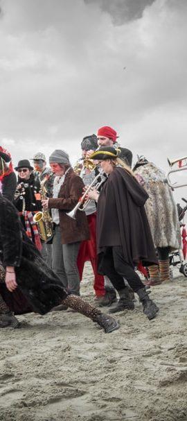 Une bande de musiciens et de carnavaleux sur la plage de Malo les bains dansant et jouant sous un ciel orageux.