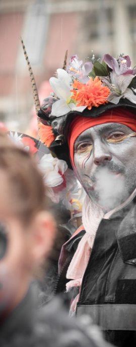 portrait de carnavaleux crachant sa fumée un femme floue au premier plan.