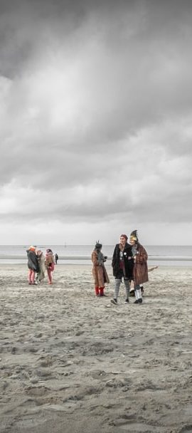 Carnavaleux sur la plage de Malo les Bains sous un ciel orageux.