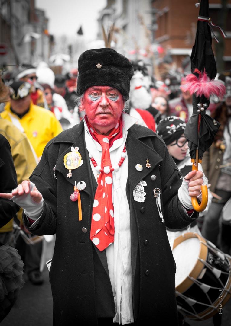 Un homme, vieux carnavaleux battant la mesure avec son parapluie et précédant la bande.