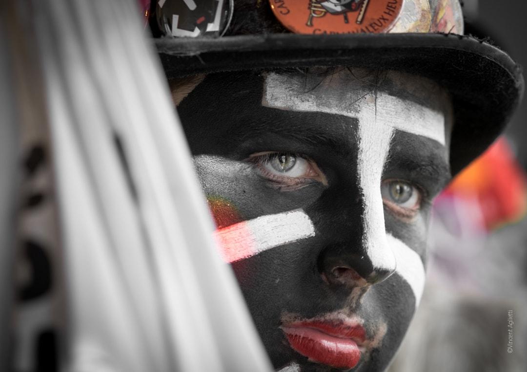 portrait d'un jeune carnavaleux maquillé en mineur, le regard lointain.