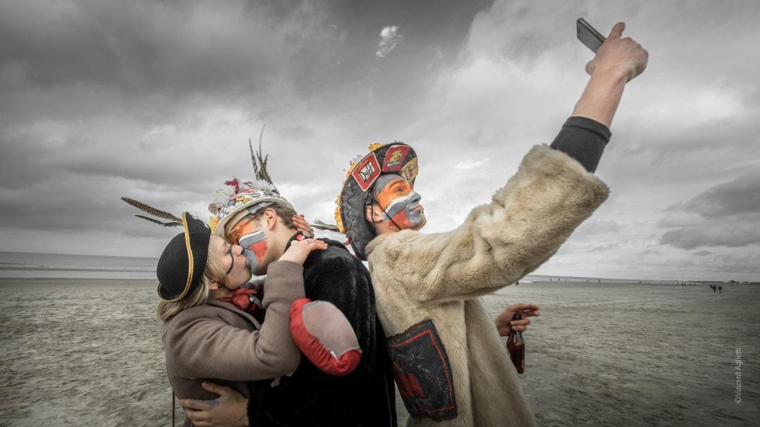 Carnavaleux sur la plage de Malo les Bains sous un ciel orageux., un couple s'embrassant et un homme photographiant en mode selfie