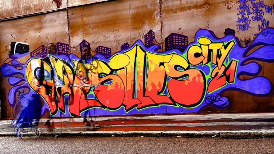Un graff dans le quartier des grésilles à Dijon. Deux passants floutés longent ce mur très coloré.