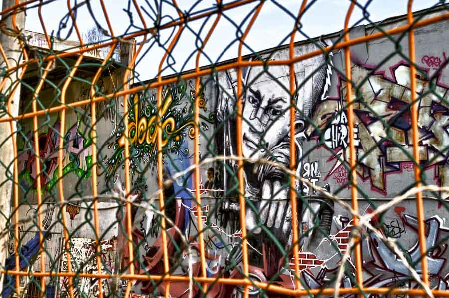 Derrière les grilles et les barbelés, les graffeurs ont peint un enfant le poing en avant. Un des graffs réalisés aux tanneries de Dijon.