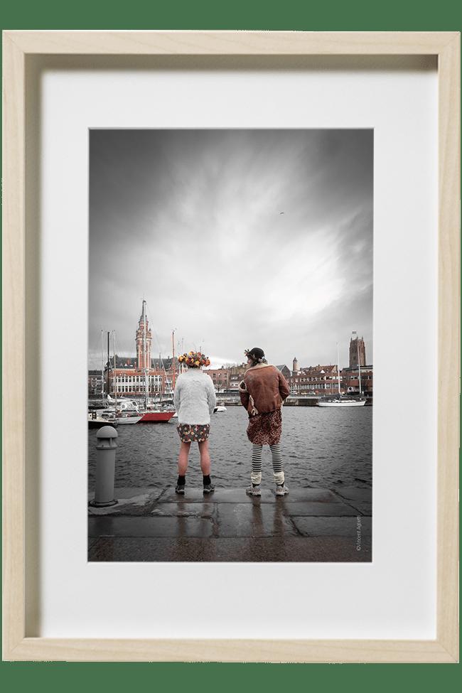 Deux carnavaleux face à la ville de Dunkerque, urinent dans le port à coté d'une bitte d'amarrage.