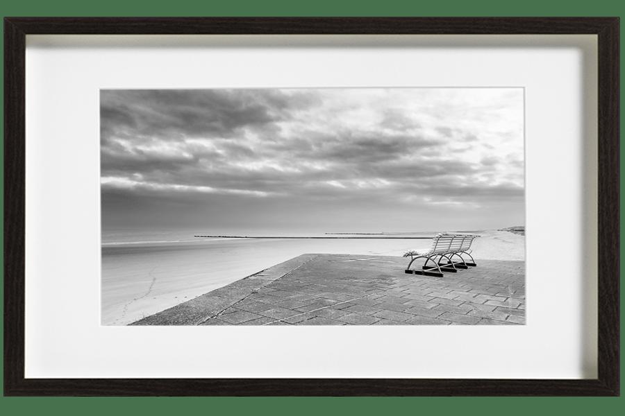 Sur les bords de la plage d'Ostende. Un banc vide surplombe le sable, des traces de pas filent vers la mer. Le ciel est menaçant.