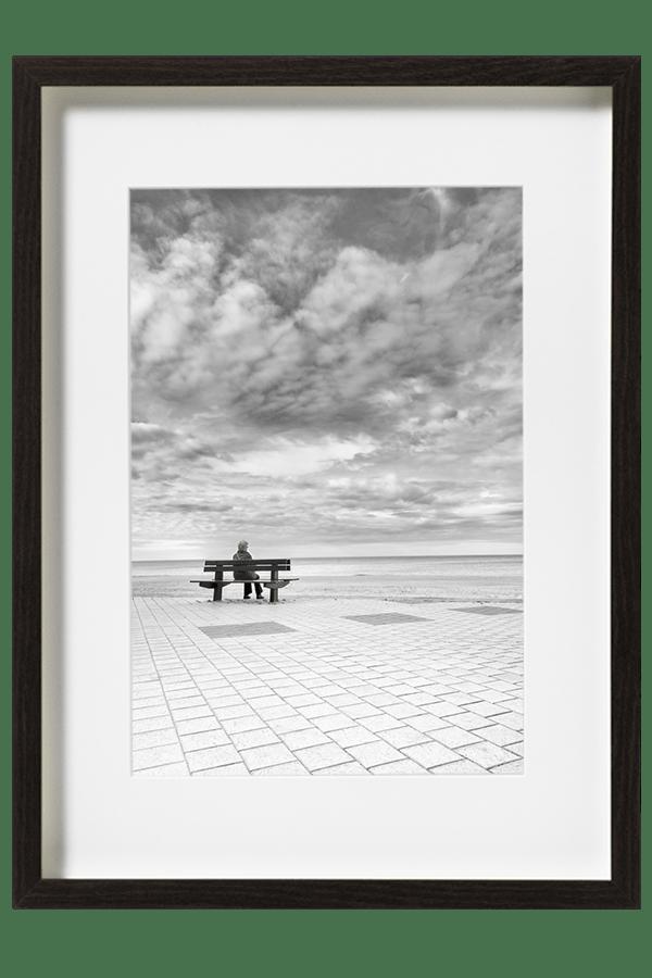 En Belgique a Knokke-Le-Zoute une femme est assise sur un banc face a la mer du Nord. Un ciel très dessiné et un trottoir bien aligné servent ce décor.