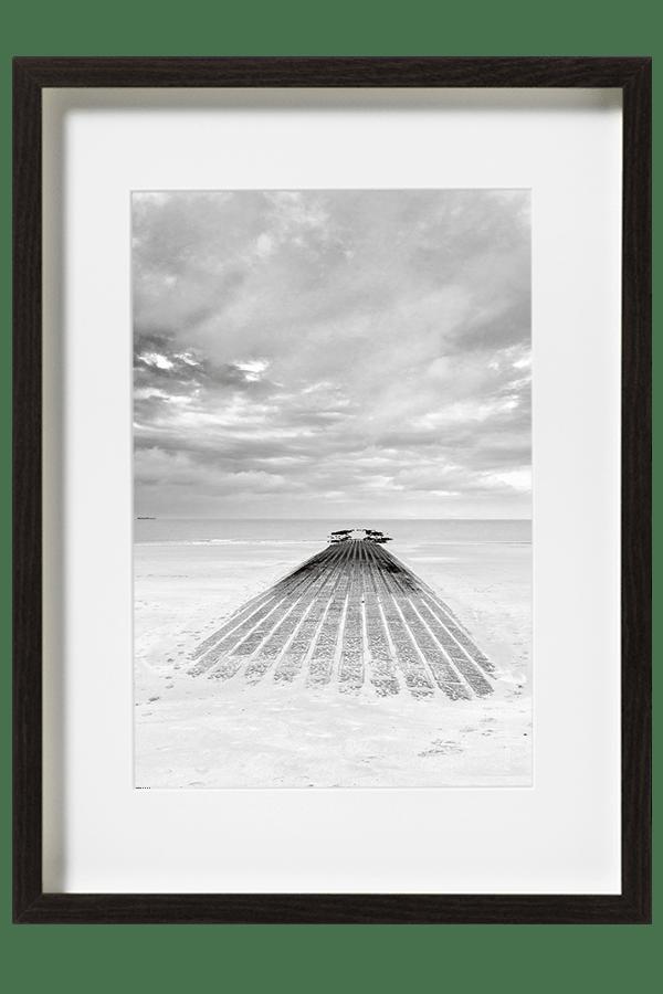 Sur la plage de knokke le zoute la mondaine, une jeté rejoint l'horizon sous un ciel orageux.