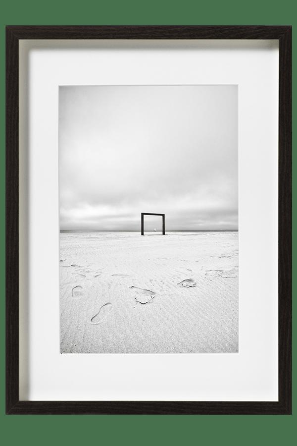 Un Portique formant un cadre naturel sur la plage de Knokke et un voilier passant au même moment.