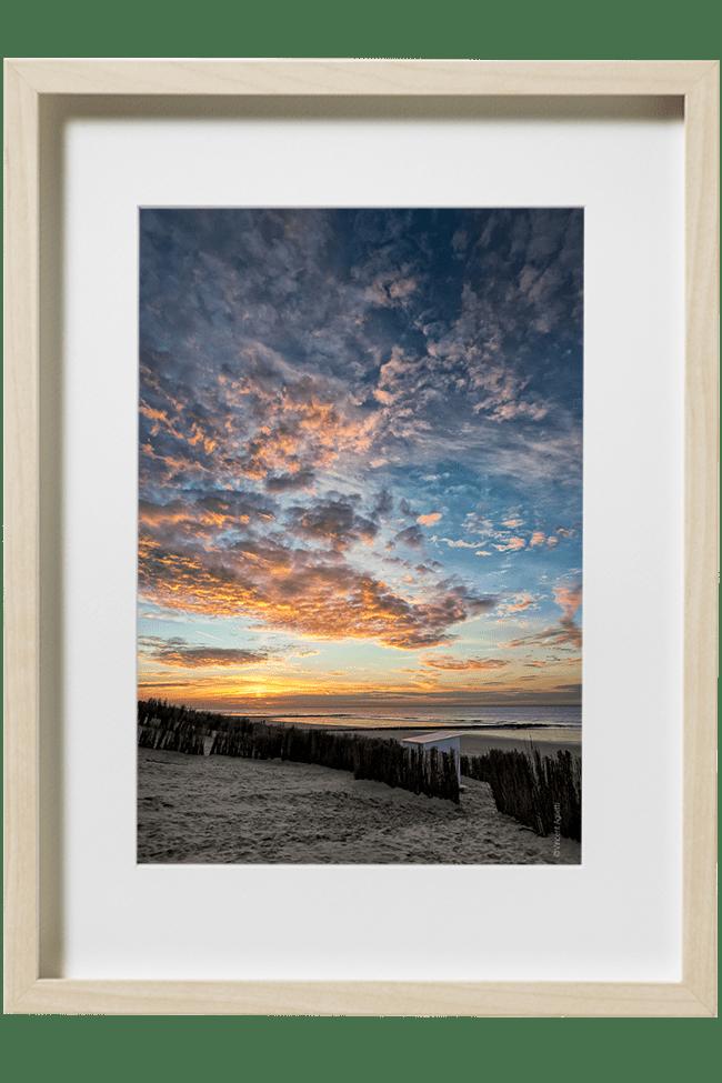Un coucher de soleil sur la mer du nord, une plage ,une cabine et des canisses contemplent ce spectacle.