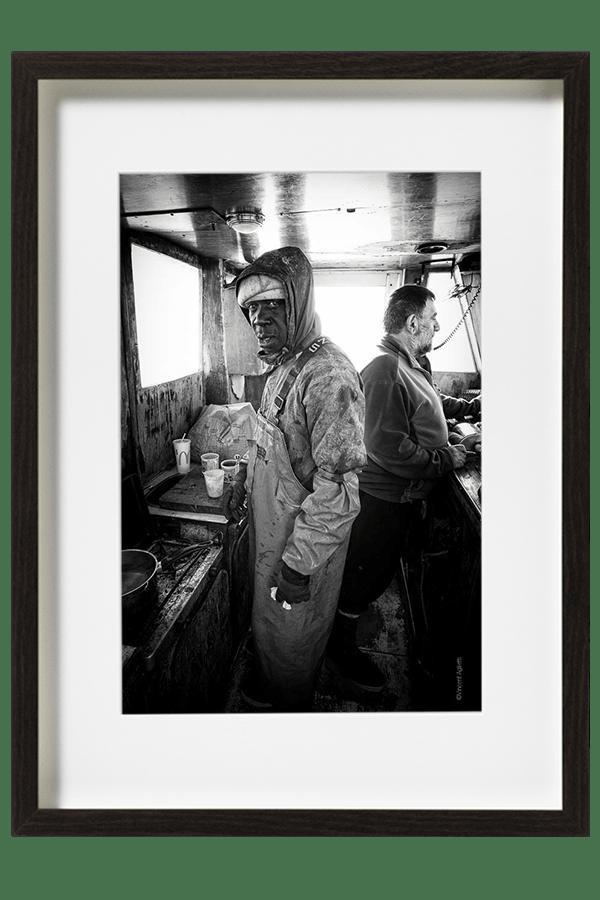 Moussa, marin pêcheur, se réchauffe dans la cabine avant de regagner les quais du port d'Arcachon.