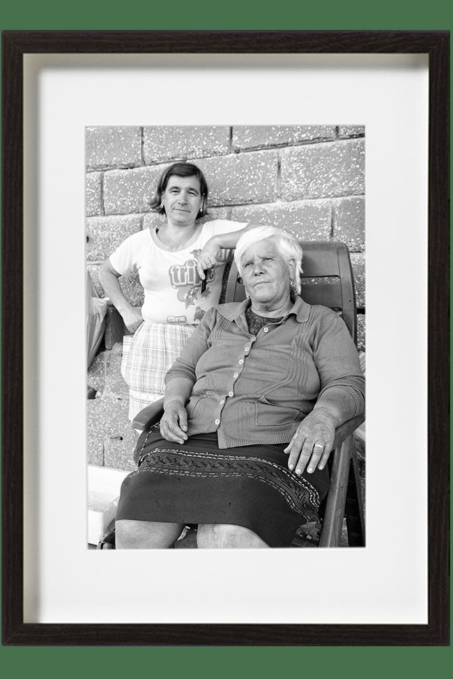 Delia et Luiza sont dockers à Nazaré, elles sont en pause l'une assise et l'autre adossée au mur. Elles offrent un regard au photographe.