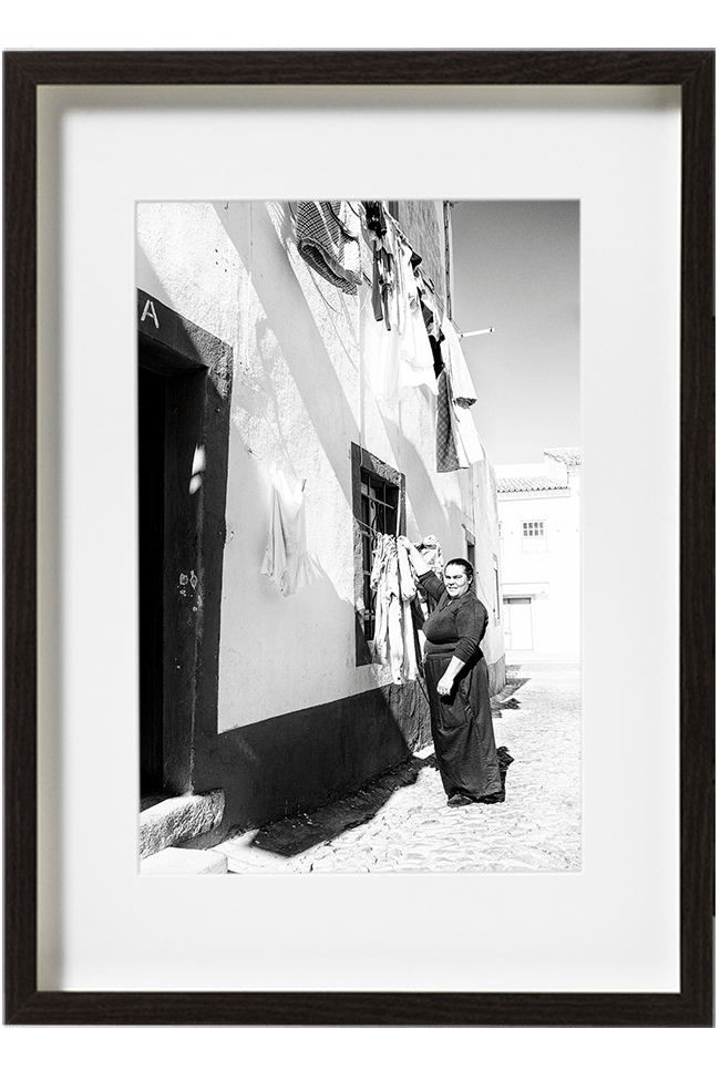 A Lisbonne, au Portugal, une femme toute vêtue de noir accroche son linge, dehors, sur l'étendoir de sa fenêtre.