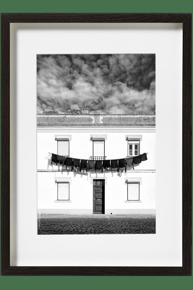 A Evora, au Portugal, du linge est accroché sur le devant d'une maison blanche et forme une longue guirlande de pulls au dessus de la porte. d'entrée.