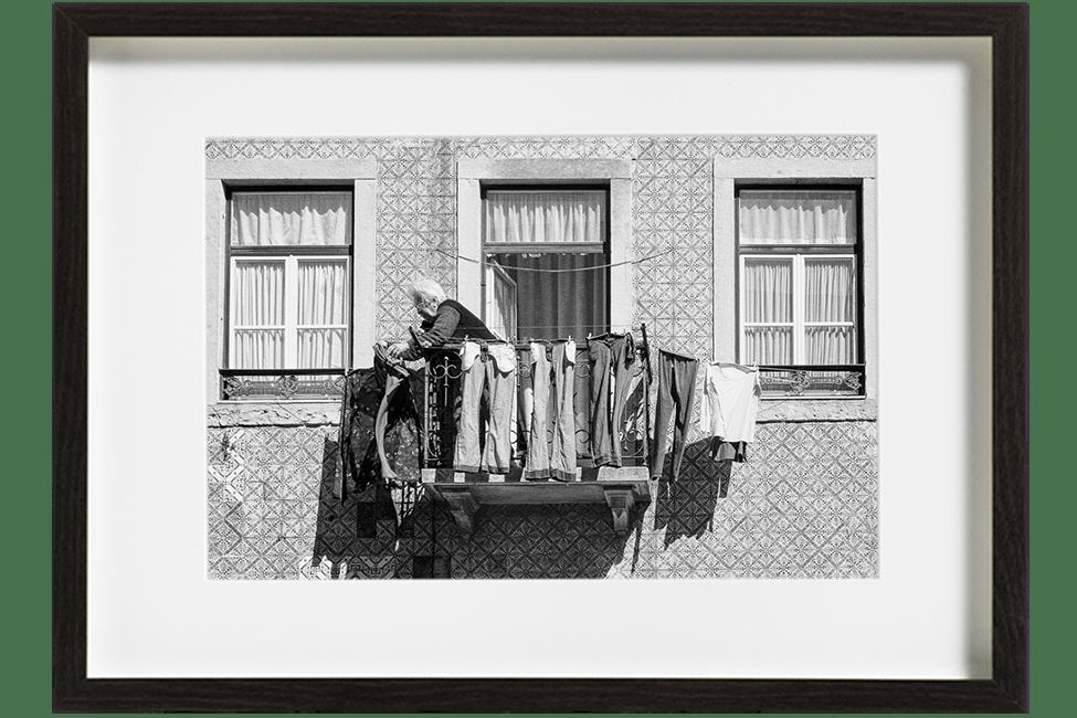 A Lisbonne, au Portugal, dans le quartier de Graca, une vieille dame aux cheveux blancs accroche son linge tout autour de son petit balcon.