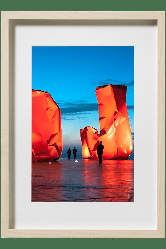 l'heure bleue sur la promenade d'Ostende. Les promeneurs déambulent au milieu des sculptures contemporaines flamandes.