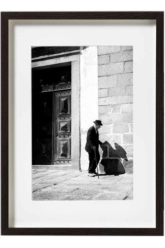 A Evora, au Portugal, un vieil homme tout vêtu de noir, chapeau sur la tête, avance tout doucement le long d'un mur à l'aide de sa canne.