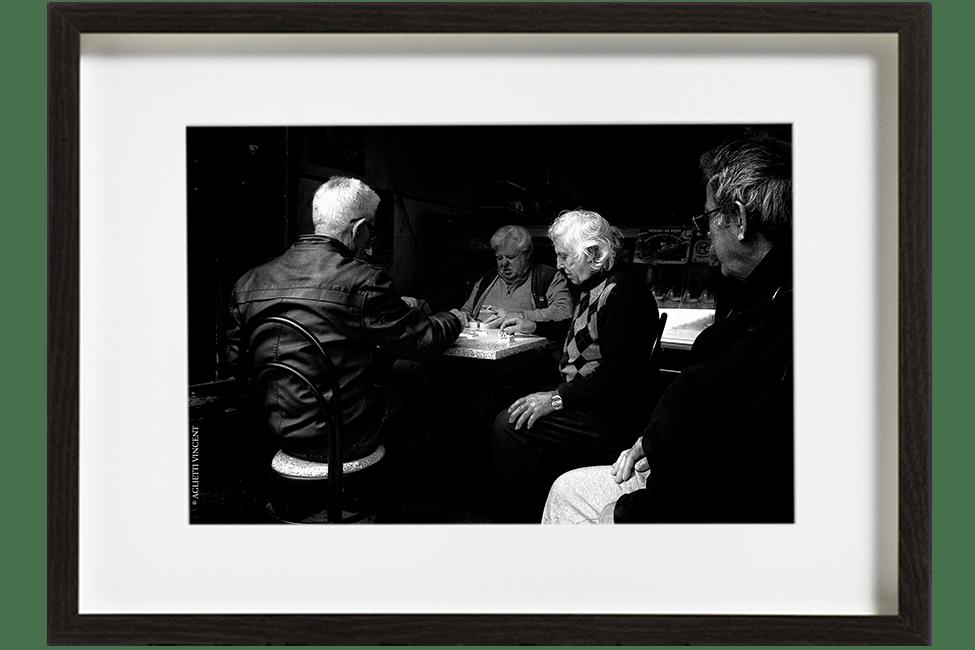A Lisbonne, au Portugal, dans le quartier de La Mouraria, 4 hommes sont assis à une table dans un café et jouent aux dominos.