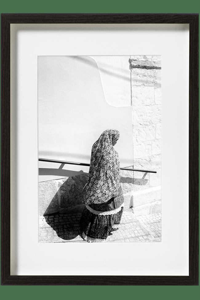 A Lisbonne, au Portugal, dans le quartier de Bica, une femme descend les escaliers. Elle porte une longue robe et est enveloppée dans un long foulard.