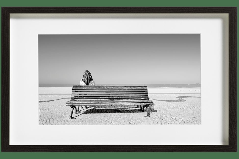 A Nazaré au Portugal, une femme assise sur un banc face à la mer, un foulard sur la tête. Au sol, une mosaïque en arabesque fuit devant elle.