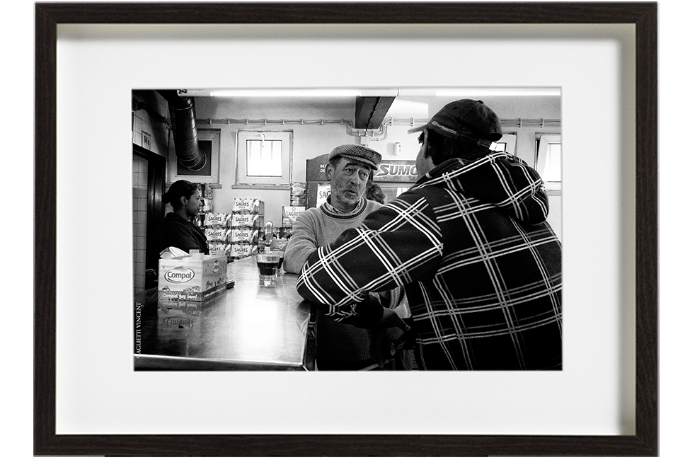 A Sinès au Portugal, deux pêcheurs sont accoudés au bar. Ils discutent face à face, le plus jeune a le dos tourné et le plus âgé porte une casquette.