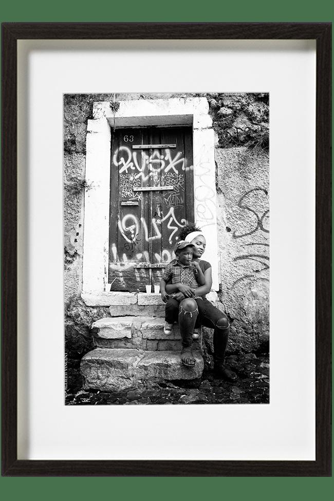 A Lisbonne, au Portugal, dans le quartier de la Mouraria, une jeune femme est assise sur les marches avec son enfant sur les genoux.