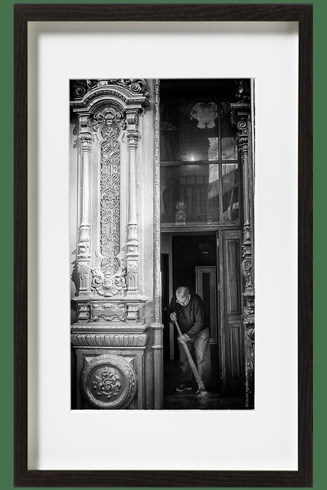 A Lisbonne, au Portugal, un homme, vêtu d'un jean et un pull noir, balaie le hall d'un immeuble dont les colonnes sont superbement sculptées.