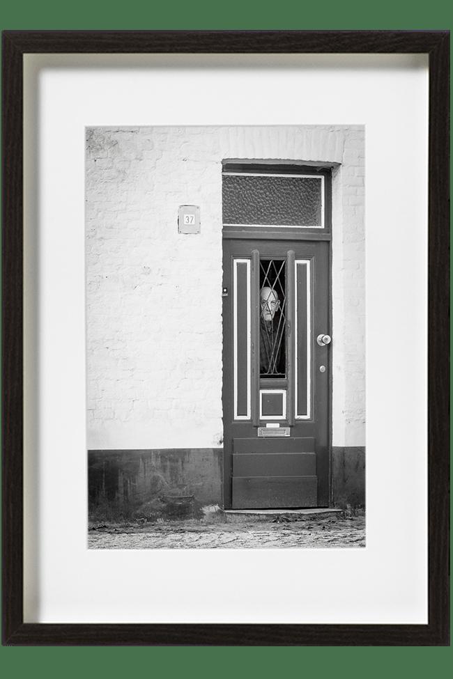 Un vieil homme visiblement noyé dans son passé, regarde le phtographe derrière la porte de sa maison.