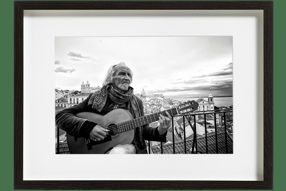 A Lisbonne, au Portugal, Will, chanteur guitariste, est assis et joue de la guitare. Derrière lui, on peut admirer la vue sur Lisbonne.