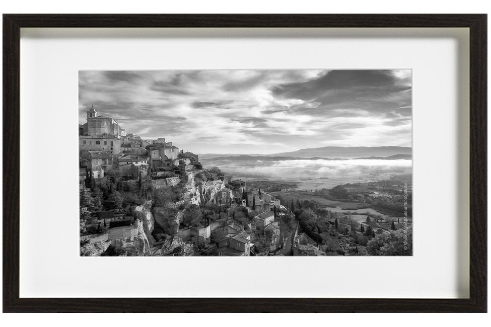 Gordes en hiver, le paysage représente le village en haut du rocher et les nuages envahissant la plaine.