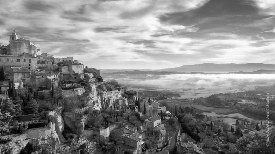 photo noir et blanc de Gordes, réalisée en hiver par Vincent Aglietti. La brume et les nuages se confondent dans la plaine.