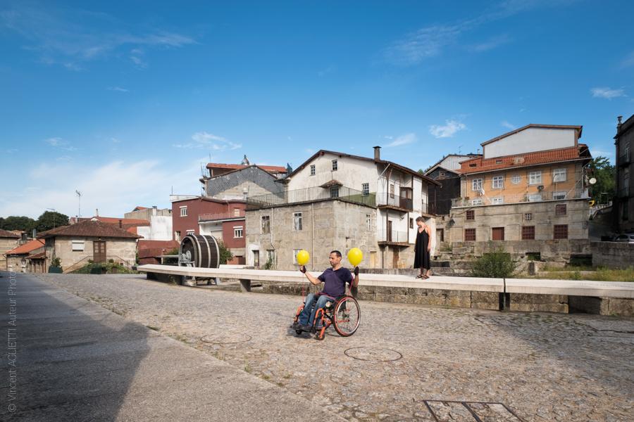 Un homme dans un fauteuil roulant tient deux ballons jaunes, une femme se tient derrière lui.Ils posent Largo do Cidade pour l'exposition Guimaraes, Aqui Nasceu Portugal de Vincent Aglietti et Vincenzo Cirillo.