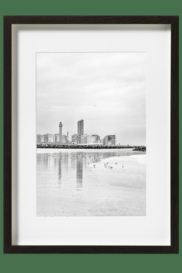 Sur la plage d'Ostende la ville se reflète sur le sable et les mouettes se regroupent dans les reflets.