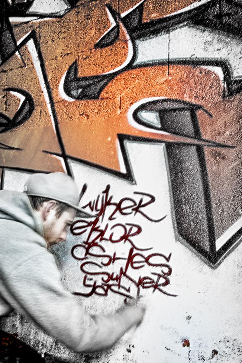 Un graffeur des tanneries termine sa fresque en signant à l'aide d'une bombe de peinture.