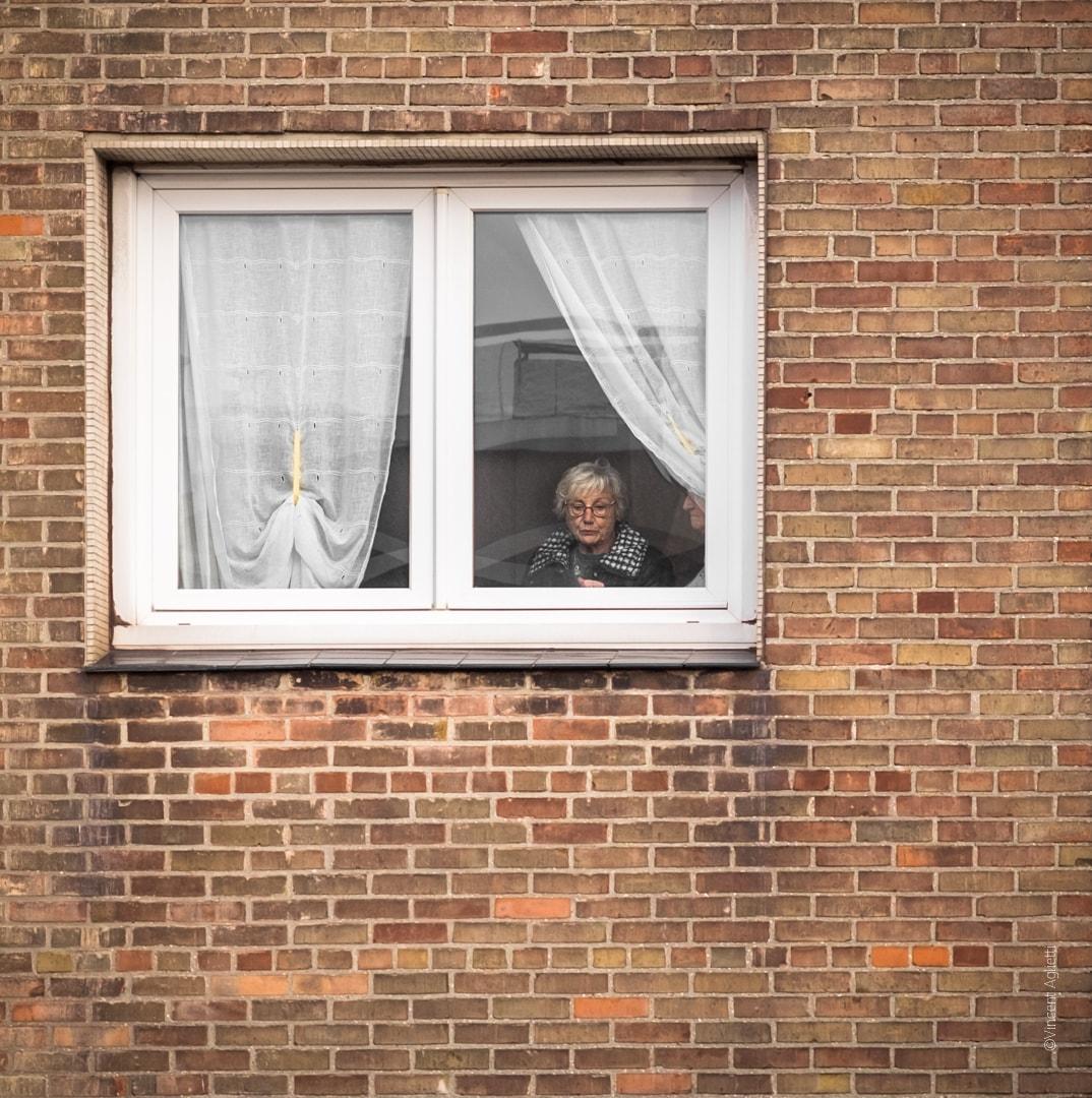 une femme derrière sa fenêtre narrant le carnaval à une autre personne,un mur de brique imposant entour cette fenêtre.