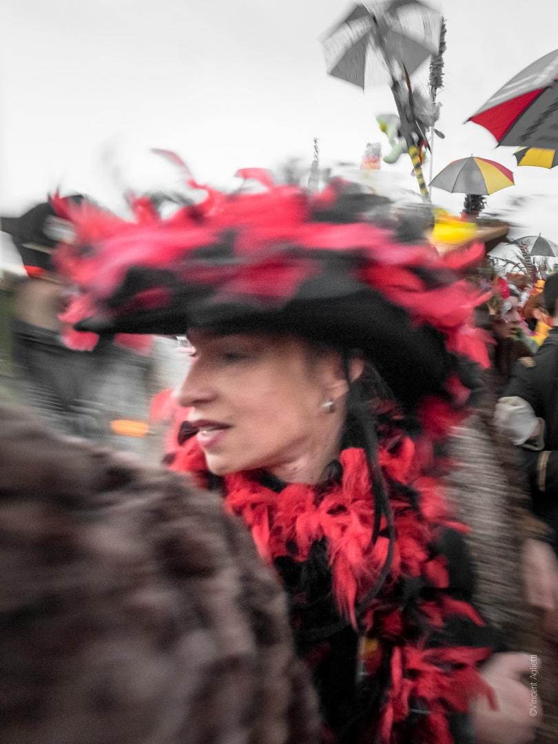 une femme au grand chapeau se retournant dans la foule dans un flou artistique.
