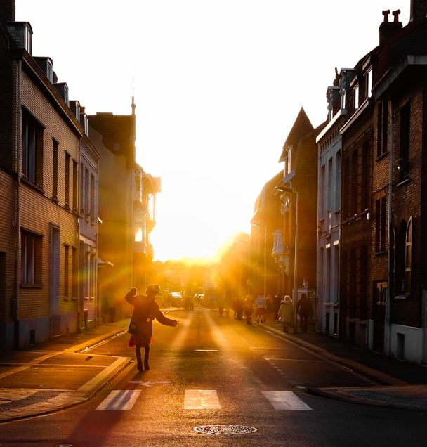 Au programme des voies off 2017.Un Carnavaleu à Dunkerque dansant en traversant un passage pieton. Le soleil.se couche