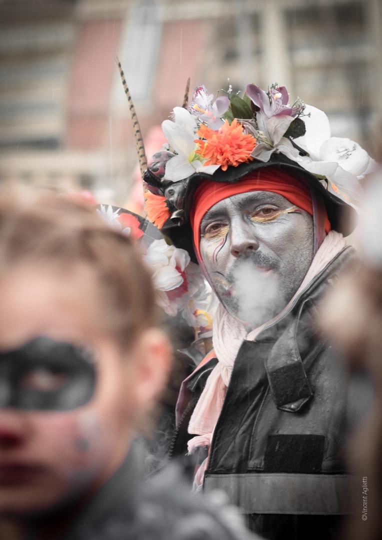 Carnaval de Dunkerque, un portrait de carnavaleux crachant sa fumée un femme floue au premier plan.