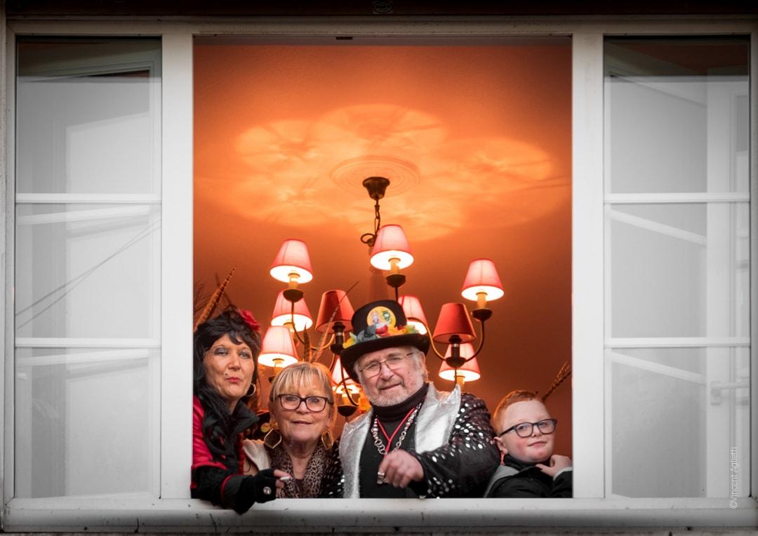 Une famille de carnavaleux à leur fenêtre attendant les invités d'une chapelle.