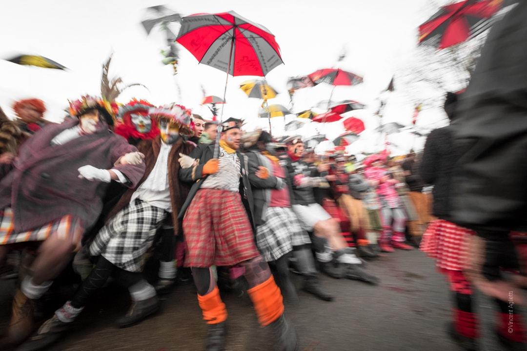 La première ligne du carnaval tenant leur berguenard et donnant la sensation de s'écrouler dans un flou artistique.