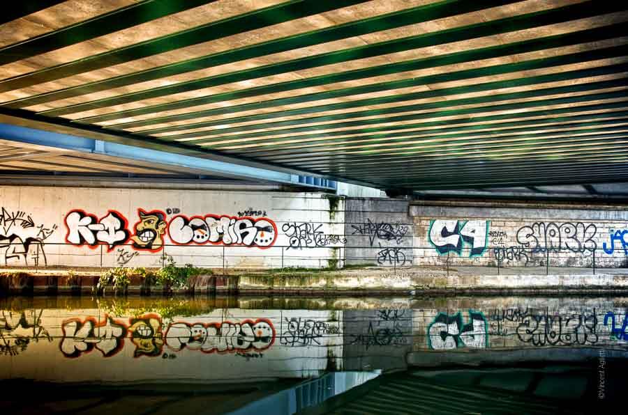 Le long du canal de Bourgogne, sous un pont, les graffs se reflètent dans l'eau.
