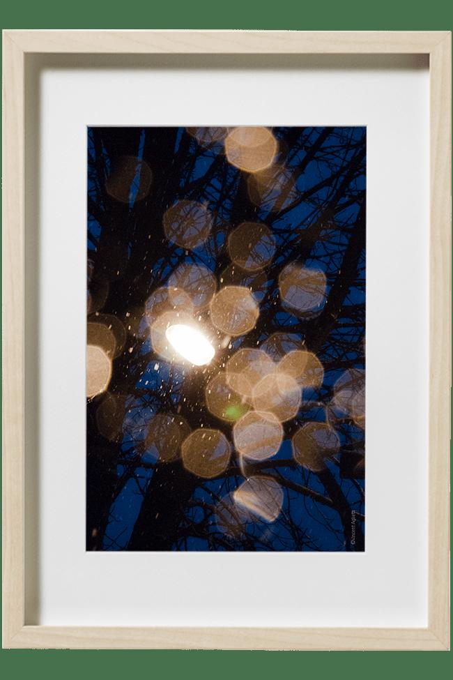 Pendant une chute de neige, un reverbère allumé envois par sa lumière sur l'objectif des cristaux.