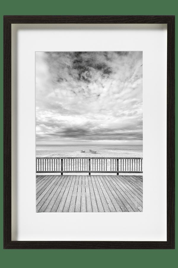 Un terrasse en bois surplombant la plage, sur le sable les paravents et accessoires s'empilent.