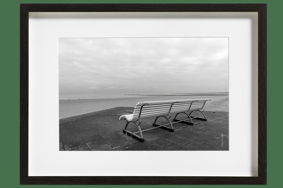 Un banc vide face a la mer du nord, la plage est vide et le ciel se couvre.