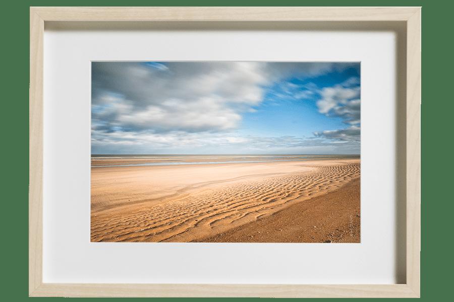 Une étendue de sable et un ciel nuageux, la mer du Nord haute en couleurs