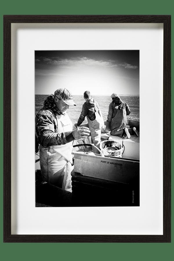 Les marins pêcheurs nettoient le pont et les casiers à grande eau. Les côtes arcachonnaises apparaissent à l'horizon.