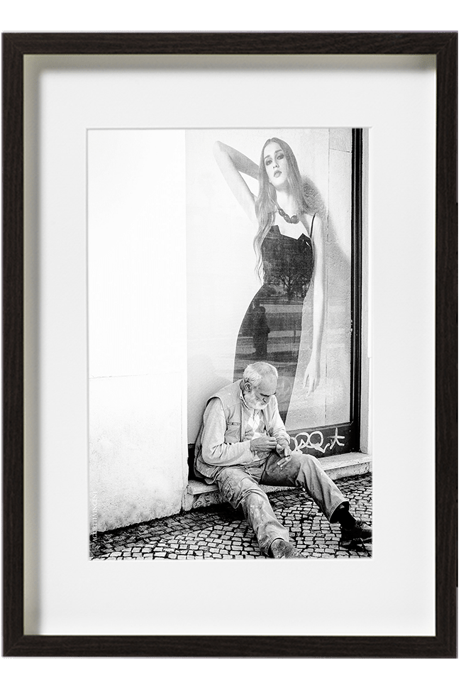 Lisbonne, Portugal, quartier de la Mouraria, un homme en vêtement de travail est assis par terre. Il est adossé contre une vitrine de magasin de mode.