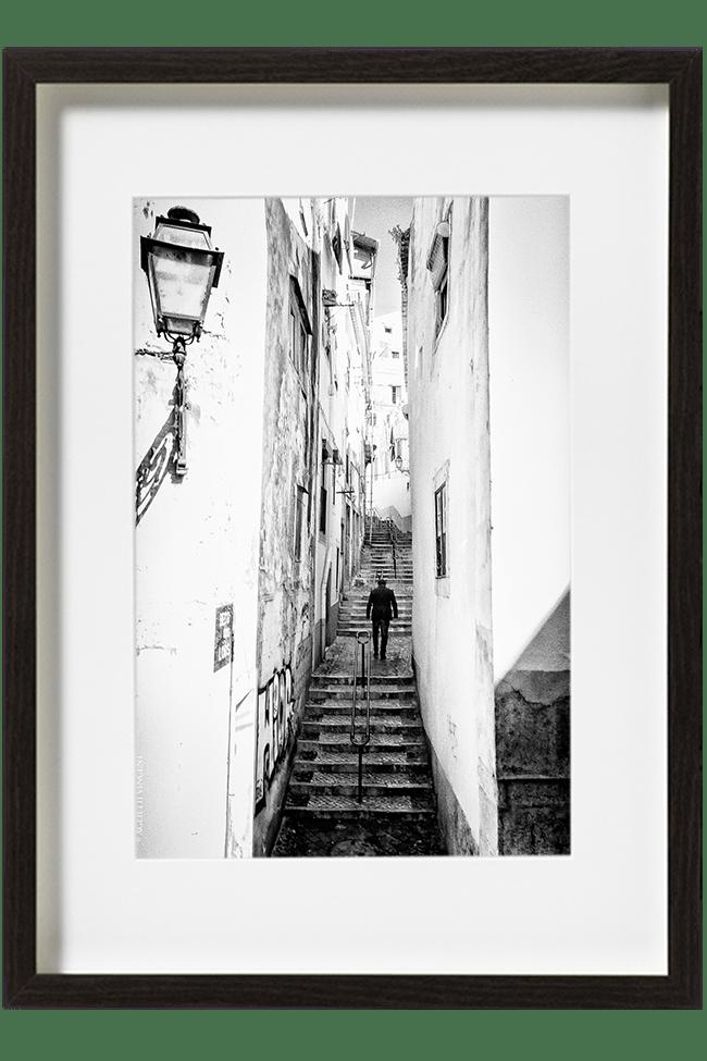 A Lisbonne, au Portugal, dans le quartier de l'Alfama, un homme remonte les escaliers d'une ruelle. Au premier plan, un réverbère.