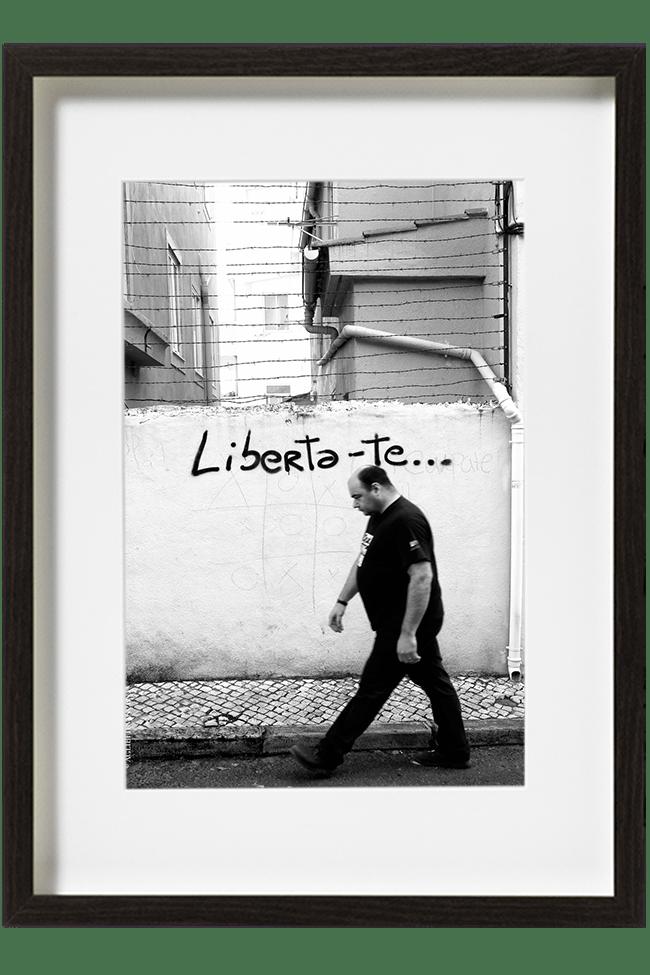 A Lisbonne, au Portugal, un homme passe, tête baissée, devant un mur sur lequel est inscrit Liberta-te. Il marche d'un pas rapide et est vêtu de noir.
