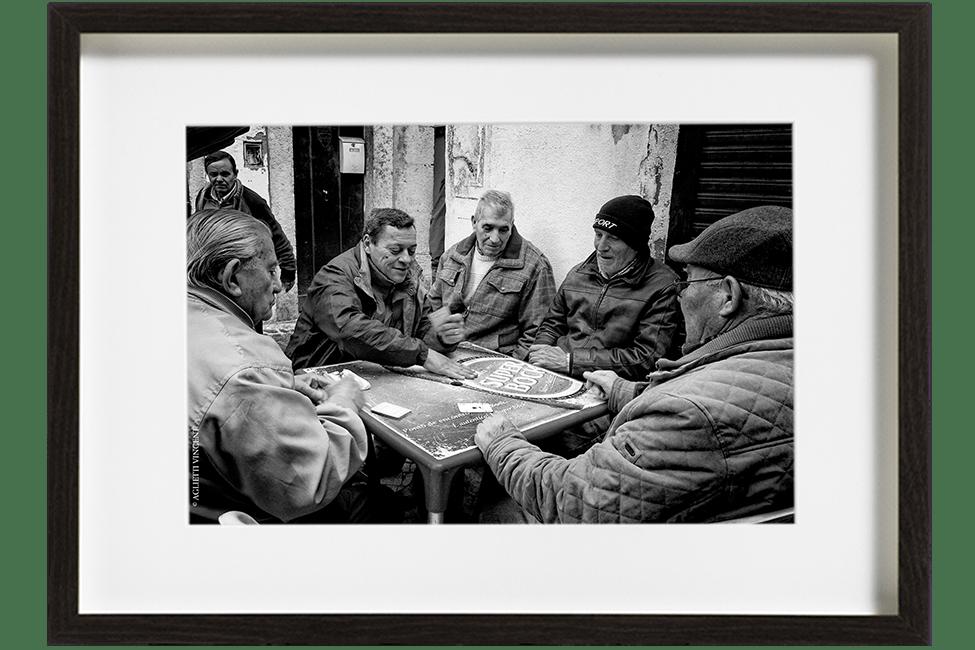 A Lisbonne au Portugal, dans le quartier d'Alfama, 5 hommes sont assis autour d'une table et jouent aux cartes. Ils partagent une partie de Sueca.